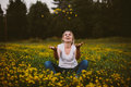 Girl sitting in field of yellow wildflowers Royalty Free Stock Photo