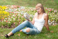Girl sitting in the garden and reading a book Stock Photos