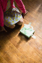 Girl sitting with gift box on wooden floor