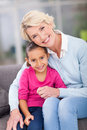 Girl sitting grandmother pretty little with her at home Royalty Free Stock Photo