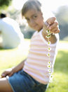 Girl (6-8) sitting on grass in park, holding daisy chain, smiling, portrait (differential focus) Royalty Free Stock Photo
