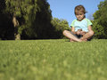 Girl sitting on grass in park listening to mp player front view surface level Royalty Free Stock Image