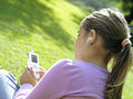 Girl sitting on grass in park listening to mp player rear view close up tilt Stock Images
