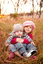 Girl Sitting With Her Baby Brother in a Field Stock Images