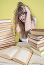 Girl sitting with lots of books and grabs his head. Royalty Free Stock Photo