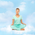 Girl sitting in lotus position and meditating Stock Photos