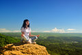 Girl sitting in the lotus position on the mountain