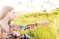 Girl sitting in a meadow in a swarm of flitting butterflies. Royalty Free Stock Photo