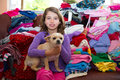 Girl sitting on a messy clothes sofa with chihuahua dog before folding laundry Stock Photo