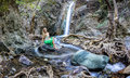 Girl sitting by the millomeri waterfalls in the troodos mountains a a green dress Stock Image