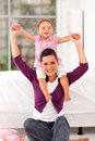 Girl sitting on mother's shoulders Stock Image