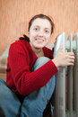 Girl is sitting near oil heater Stock Photo