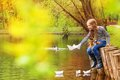 Girl sitting near pond playing with paper boats the on the water in beautiful forest landscape Stock Image