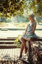 Girl is sitting on the parapet blonde in a hat a stone in park and looking away Royalty Free Stock Image