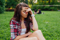 Girl sitting in  the park on the grass. She has headache. What a Royalty Free Stock Photo