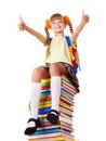 Girl sitting on pile of books showing thumbs up. Stock Photography