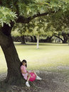 Girl sitting on pink space hopper beneath tree in park smiling side view Stock Photos