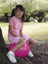 Girl sitting on pink space hopper beneath tree in park smiling side view portrait Stock Images