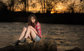 Girl sitting on a river rock young white caucasain female near during sunset staring out into the distance Royalty Free Stock Images