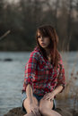 Girl sitting on a river rock young white caucasain female near during sunset staring out into the distance Stock Photos