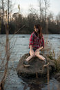 Girl sitting on a river rock young white caucasain female near during sunset staring out into the distance Royalty Free Stock Photography