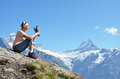 Girl sitting rock against swiss alps Stock Image