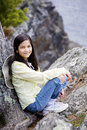 Girl sitting on rock cliff edge Royalty Free Stock Image