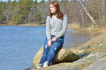 Girl sitting on rock a teenage a in front of the sea during spring in sweden Stock Photos