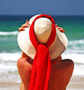 Girl sitting on sandy beach in the sun adjusting hat. Blue sky, blue sea red scarf. Spain. Stock Photos