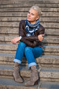 Girl sitting on the stairs in leather jacket Royalty Free Stock Images