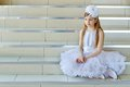 Girl sitting on the steps pretty little in white dress Royalty Free Stock Images