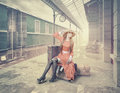 The girl sitting on the suitcase waiting at retro railway station vintage color cards style Royalty Free Stock Image