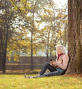 Girl sitting by a tree in park and writing sms shot with tilt shift lens Royalty Free Stock Photo