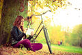 Girl is sitting under the tree with her bike. Royalty Free Stock Photo