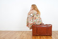 Girl sitting on a vintage suitcase, waiting Royalty Free Stock Photo