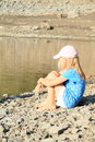Girl sitting by water little barefoot in blue t shirt with cherries shorts and cap on stone ground a lake Stock Images