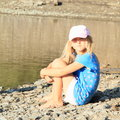 Girl sitting by water little barefoot in blue t shirt with cherries shorts and cap on stone ground a lake Royalty Free Stock Photography