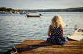 Girl sitting in wooden jetty Royalty Free Stock Photo