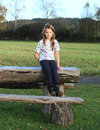 Girl sitting on wooden table little kid brunette meadow Royalty Free Stock Photography