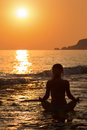 Girl sitting in a yoga pose on the beach beautiful view of at sunset Royalty Free Stock Images