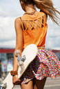 Girl with skateboard sexual woman walking on street urban style view from the back outdoors lifestyle Stock Photo