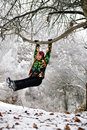 Girl in ski suit on tree in snowy winter Stock Photo