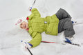 Girl with skiing, sticks lie on snow Royalty Free Stock Photos