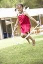 Girl skipping in garden Stock Photos