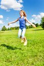 Girl with skipping rope beautiful jumping in the park on green grass field on sunny summer day Stock Photo