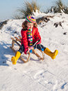 Girl sledging smiling enjoys down a snow covered dune Royalty Free Stock Images