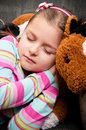 Girl sleeping with teddy bear portrait of cute young a Stock Photos