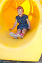 Girl slide playground pipe kid child yellow dynamic laughing Stock Photography