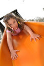 Girl on the slide slides headlong from chute Royalty Free Stock Photos