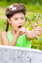 Girl with slingshot in summer Stock Images